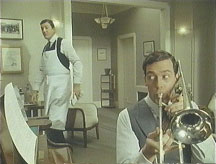 Bertie Wooster plays trombone while Jeeves looks askance.